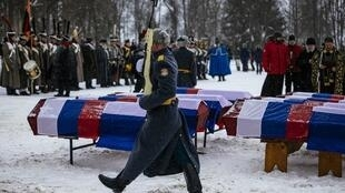 A Russian honour guard passes by coffins containing remains of Russian and French soldiers during a burial ceremony in the western town of Vyazma on February 13, 2021.