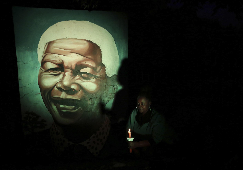 Une habitante de Soweto éclaire à la bougie une peinture murale de Nelson Mandela, le 4 décembre 2014.