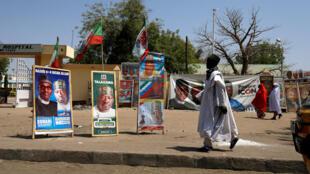 A Maiduguri, un homme passe devant des affiches de campagne après le report des élections au Nigeria, le 17 février 2019.