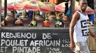 Un homme passe devant un restaurant à Abidjan en Côte d'Ivoire, en novembre 2017.