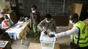 Une femme vote dans un bureau de vote lors de l'élection présidentielle à Abidjan, Côte d'Ivoire, le 31 octobre 2020.