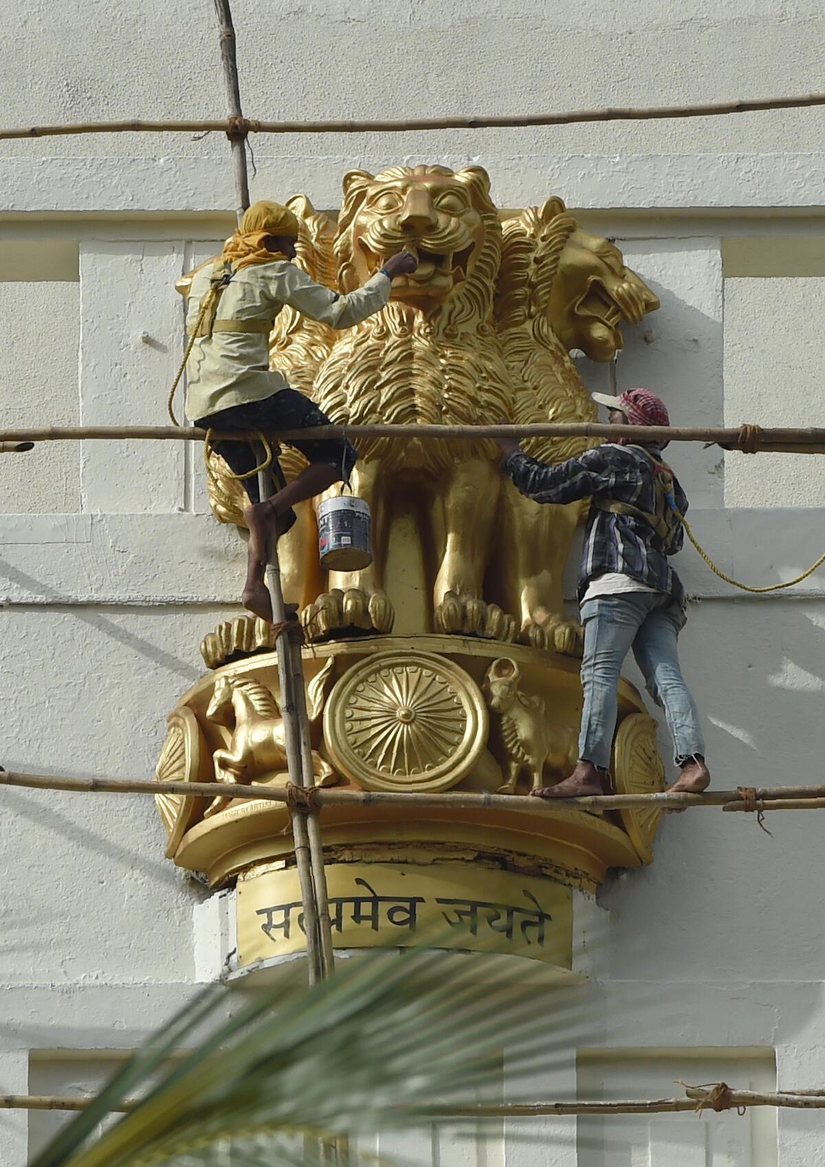 Sur la façade du Secretariat de Bombay, des manoeuvres repeignent l'emblème national composé d'un chapiteau aux trois lions du pilier d'Ashoka. Symbole du «making of» d'une nation.