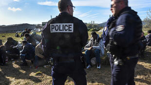 French police stand over a group of migrants and refugees eating a meal provided by a local NGO in Calais