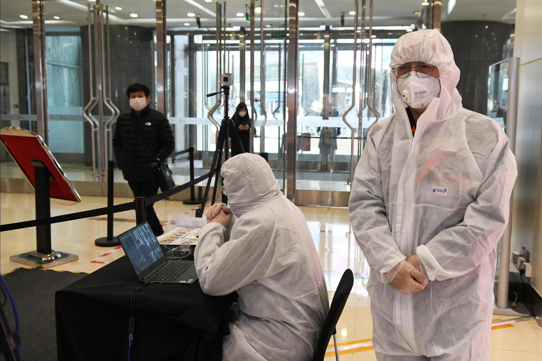 Nhân viên bảo vệ một trung tâm thương mại tại Bắc Kinh, Trung Quốc, kiểm tra thân nhiệt khách hàng. Ảnh chụp ngày 27/02/2020