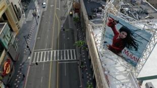 Une affiche du film «Mulan» des studios Walt Disney qui devait sortir le 27 mars, domine un Hollywood Boulevard vide lors de l'épidémie de Covid-19, à Hollywood, Los Angeles , le 31 mars 2020.