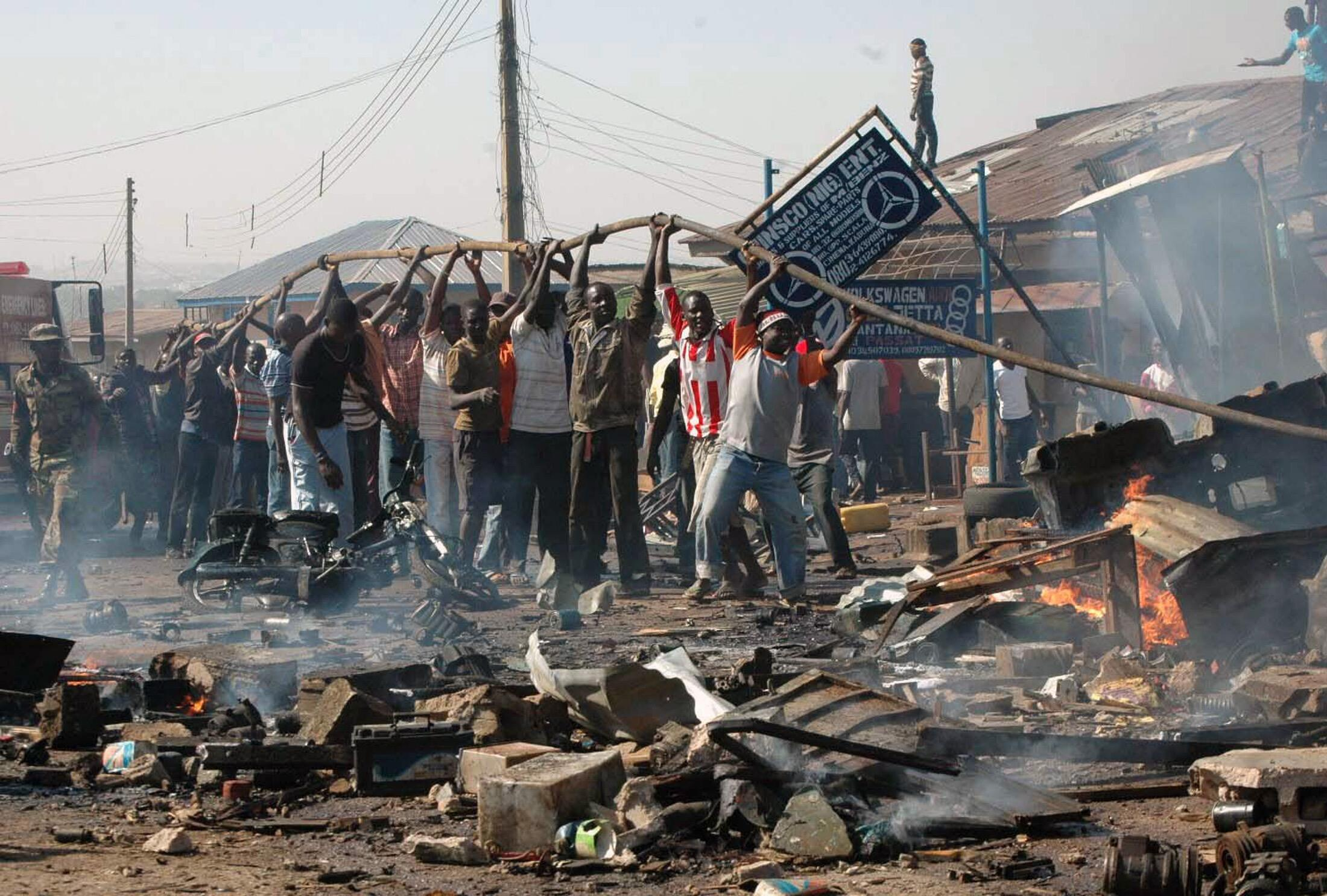 People help to carry a water hose as they try to put a fire at the scene of a bomb explosion in Kaduna, Nigeria