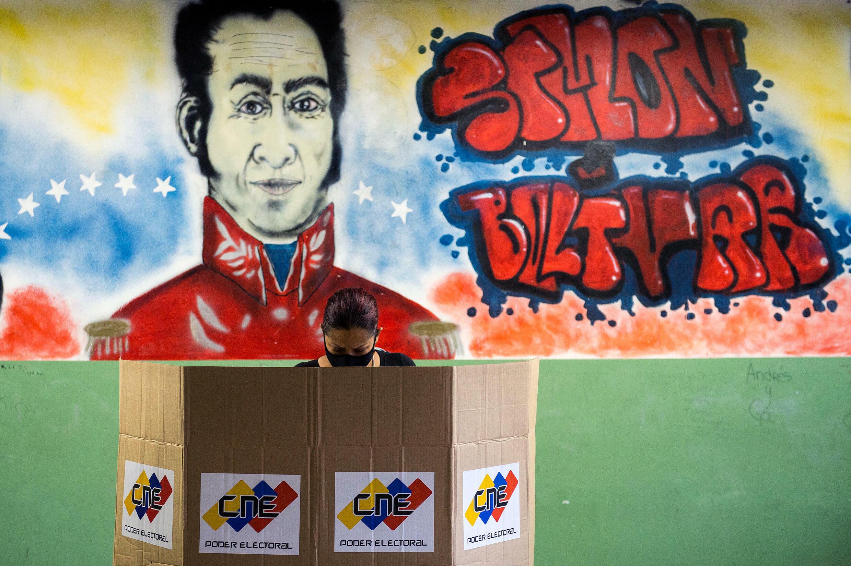 Una mujer emite su voto en un centro de votación en una escuela de Caracas, el 6 de diciembre de 2020, durante las elecciones legislativas de Venezuela
