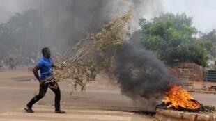 Un manifestant lance des branchages dans un brasier, à l'intersection de plusieurs rues, à Ouagadougou ce 18 septembre.