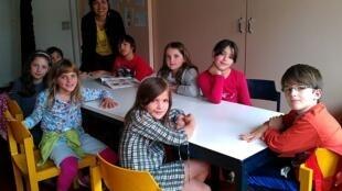 A professora Mione Hugon com as crianças que participam da oficina de literatura.