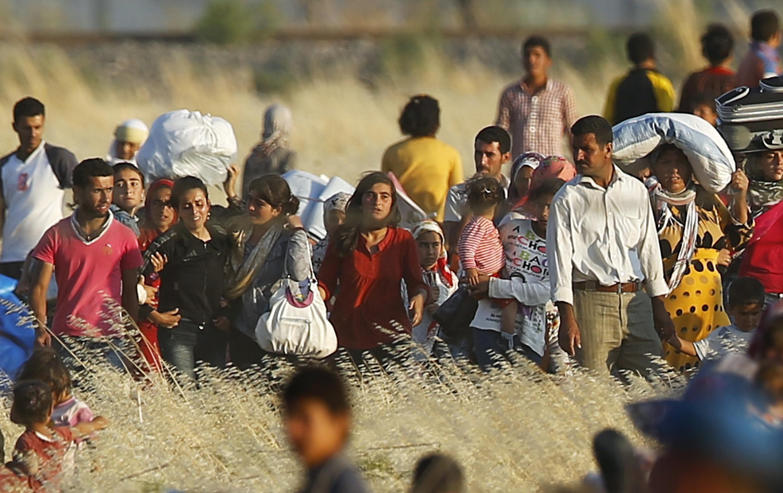 Des Kurdes syriens de Kobané marchent en direction de la frontière turque, en juin 2015 (photo d'illustration).