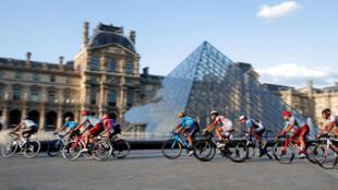 Le peloton passant devant la pyramide du Louvres à Paris lors de la dernière étape du Tour de France 2019  entre Rambouillet et les Champs Elysées, le 28 juillet.