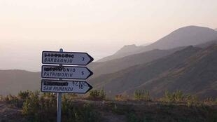 FLNC graffiti on a roadsign in Corsica; French town names have been removed.