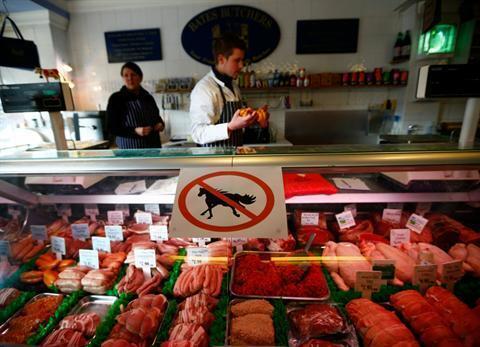 "Butcher works behind a ""no horsemeat"" sign"