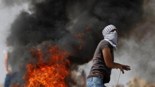 Un Palestinien durant des affrontements avec les forces israéliennes dans le village de Khobar, près de Ramallah, le 22 juillet 2017. La veille, trois Israéliens ont été tués dans l'implantation juive de Neve Tsuf par un Palestinien originaire de Kobar.