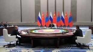 Vladimir Putin (esquerda), Xi Jinping (centro) e presidente da Mongólia, Khaltmaagiin Battulga, discutem durante a cúpula da Organização para a Cooperação de Xangai, em Qingdao, no leste da China.