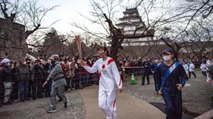 L'ancienne joueuse de volley-ball Motoko Obayashi (c.) court avec la flamme lors de la dernière étape du deuxième jour du relais de la flamme des Jeux olympiques de Tokyo 2020 au château de Tsurugajo dans la ville d'Aizuwakamatsu, préfecture de Fukushima, le 26 mars 2021.