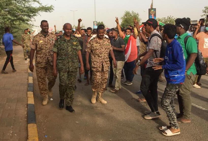 Des manifestants saluent des soldats près du quartier général militaire dans la capitale soudanaise.