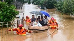 Des sauveteurs évacuent des résidents de la ville Jiujiang, touchés par les crues dues aux pluies torentielles dans la province du Jiangxi au centre de la Chine, le 8 juillet 2020.