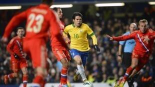 Kaká corre entre os russos, em partida amistosa em Londres, nesta segunda-feira (25/03).