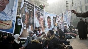 Manifestants devant les portraits des personnes tuées depuis le soulèvement en Egypte, le 11  février au Caire.