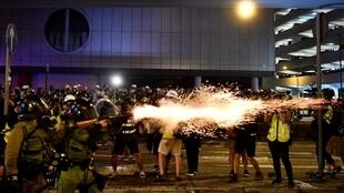 A policeman fires tear gas at protesters to disperse them after a march against a controversial extradition bill in Hong Kong, 21 July 2019.
