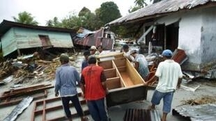 Local residents salvage materials from their destroyed homes in the tsunami-hit hamlet of Malakopa