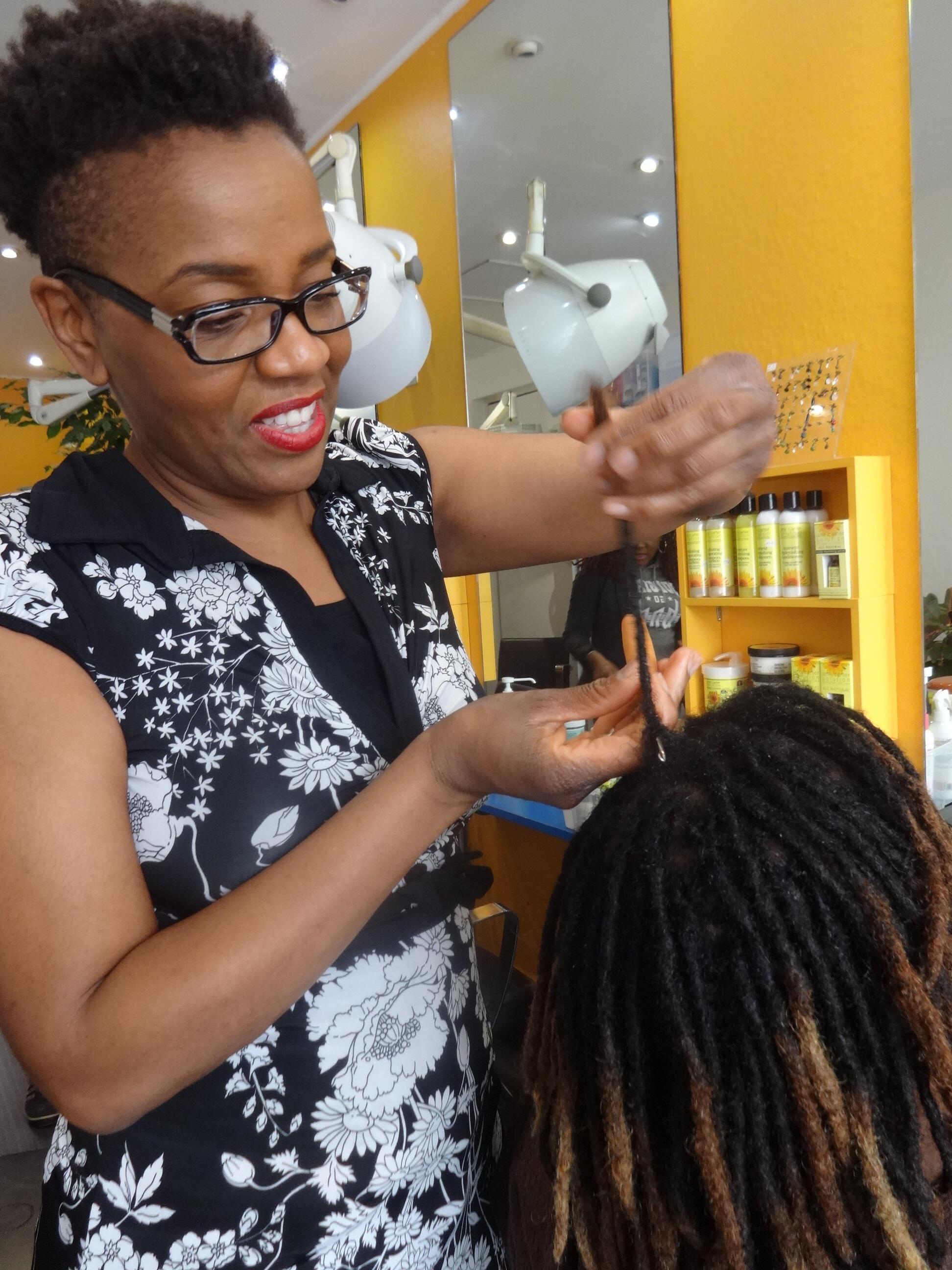 Aline Tacite works on a client's dreadlocks in her hair salon, Boucles d'ébène.
