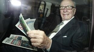 News Corporation CEO Rupert Murdoch holds a copy of The Sun and The Times as he is driven away from his flat in central London