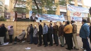 People stand in line outside a polling station as they wait to cast their votes during parliamentary elections in Cairo