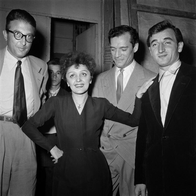 """ادیت پیاف خوانندۀ شهیر فرانسوی در کنار """"میشل اِمر""""، آهنگ ساز فرانسوی، """"ادی کنستانتین""""، هنرپیشۀ آمریکایی، و شارل آزناوور در سال ۱٩۵٠ در پاریس."""