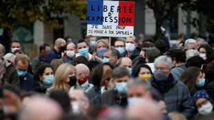 People attend a tribute to Samuel Paty, the French teacher who was beheaded on the streets of the Paris suburb of Conflans St Honorine, at the Place de la Republique, in Lille, France, October 18, 2020.