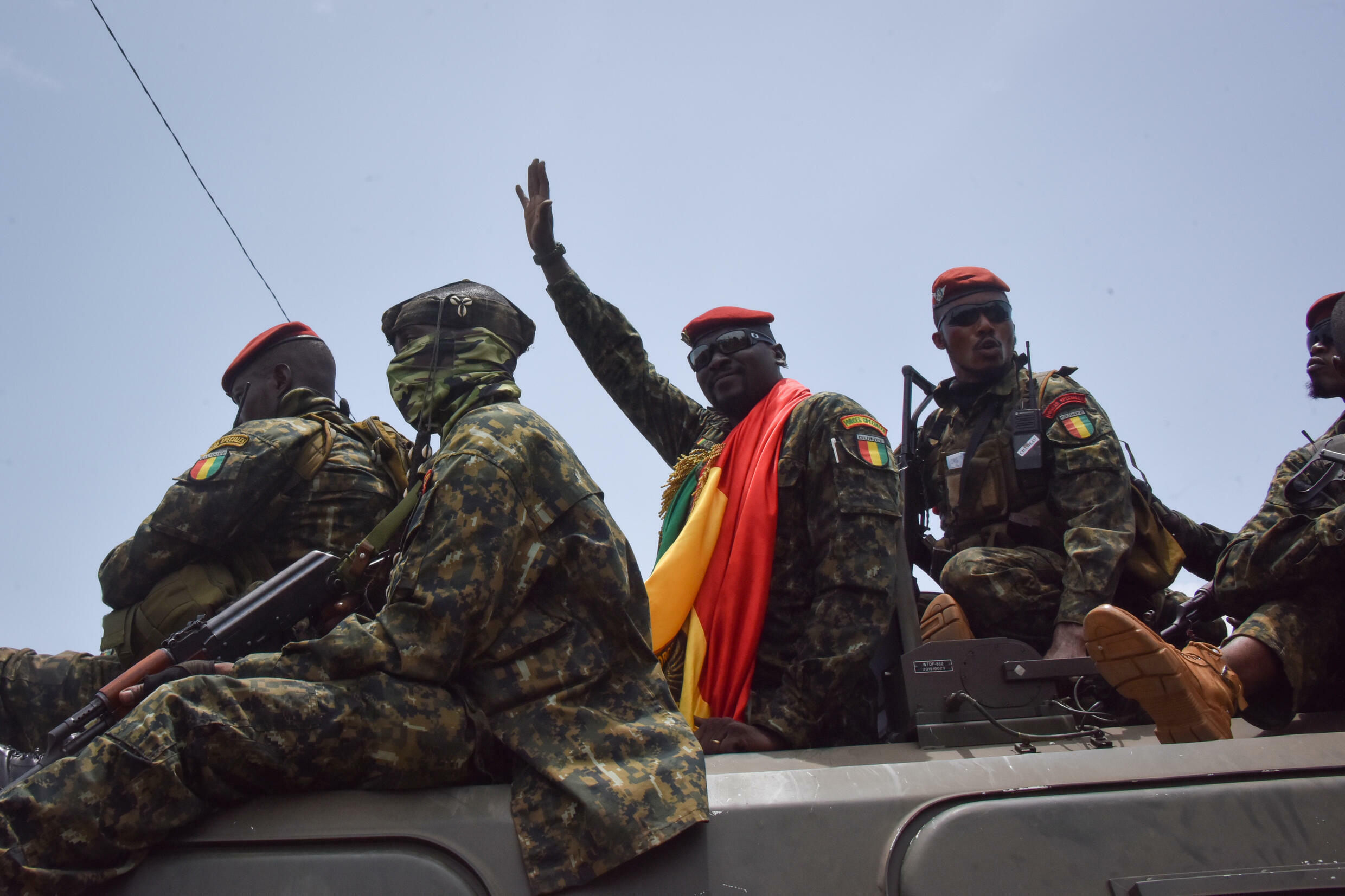 Coup leader Lieutenant Colonel Mamady Doumbouya, centre, waving to the crowd as he arrived at parliament on Monday for a meeting with outgoing ministers