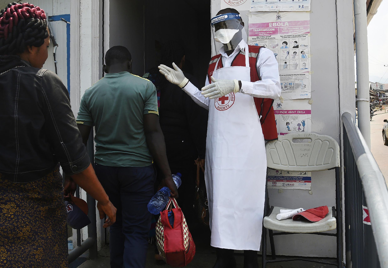 Un agent de santé accueillie des personnes au centre de dépistage sanitaire de Mpondwe, à la frontalière entre l'Ouganda et la République démocratique du Congo, le 13 juin 2019.
