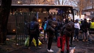 Des hommes portent leurs affaires lors de l'évacuation d'un camp de fortune de migrants et de réfugiés entre la Porte de la Villette et la Porte de la Chapelle, au nord de Paris, le 31 janvier 2019.