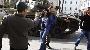A Tunisian woman poses with a soldier in front of a tank in downtown Tunis