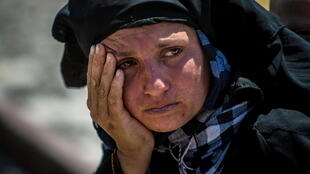 A woman reacts as she rests from walking back to Tel Abyad town, Raqqa governorate, after fleeing Maskana town in the Aleppo countryside June 16, 2015. REUTERS/Rodi Said