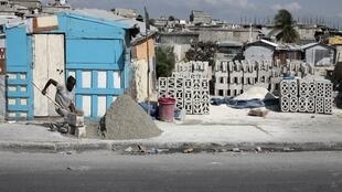 Threatened again - a Haitian rebuilds after last year's earthquake