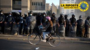 Liban: une manifestante passe devant un cortège de forces de l'ordre, le 28 avril 2020 à Beyrouth.