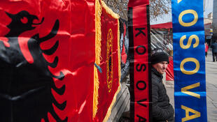 Un Albanais du Kosovo se tient à côté des drapeaux de l'Albanie et du Kosovo, à Pristina, le 16 février 2018.