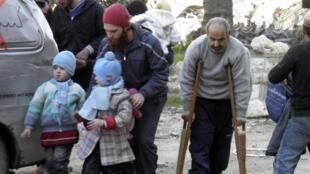 Des civils syriens marchent vers un point d'évacuation à Homs, le 9 février 2014.