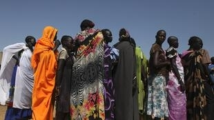 Women displaced by the conflict wait in line for registration at a camp for displaced people in Juba, 8 March 2014.