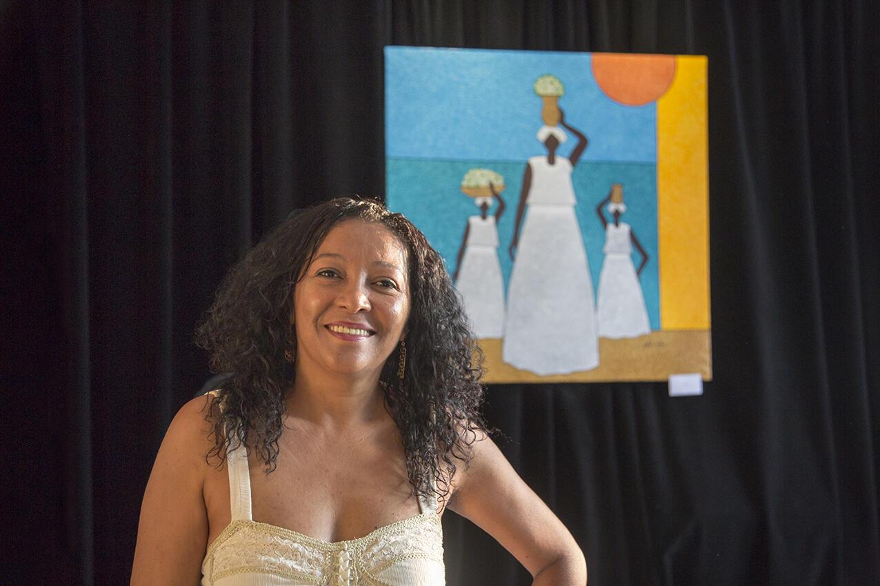 Miriam Merci posa diante de um de seus quadros expostos na sede da Associação Chant des Hommes