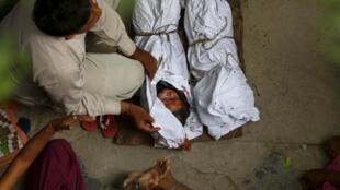 """Thi thể của hai người con của một gia đình """"tiện dân"""" bị chết trong vụ cháy tại làng Sunpedh, Ballabhgarh, bang Haryana, Ấn Độ, ngày 21/10/2015."""