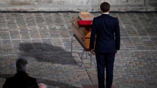 Le président Emmanuel Macron se recueille devant le cercueil de Samuel Paty, pendant l'hommage national à La Sorbonne à Paris, le 21 octobre 2020.