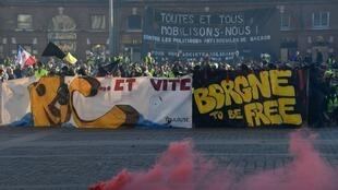 Protesters stand amid tear gas smoke during an anti-government demonstration called by the Yellow Vest movement in Toulouse on February 23, 2019.