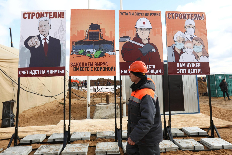 Một công nhân đi ngang qua các tấm tranh cổ động nặng phong cách Liên Xô cũ tại công trường xây dựng một bệnh viện mới dành cho bệnh nhân Covid-19, ở ngoại ô Matxcơva. Ảnh chụp ngày 21/03/2020.