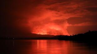 Vista general del humo y llamas en la erupción volcánica del Nyiragongo desde la isla de Tchegera en el lago Kivu, cerca de Goma, en la República Democrática del Congo el 22 de mayo de 2021.