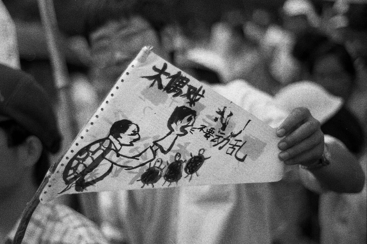 """""""Puppet play"""": a turtle symbolising China's leader Deng Xiaoping, holds a puppet symbolising Li Peng, the Prime Minister, saying """"No chaos!"""", in reference to Beijing's denunciation of the student movement as """"anarchic""""."""