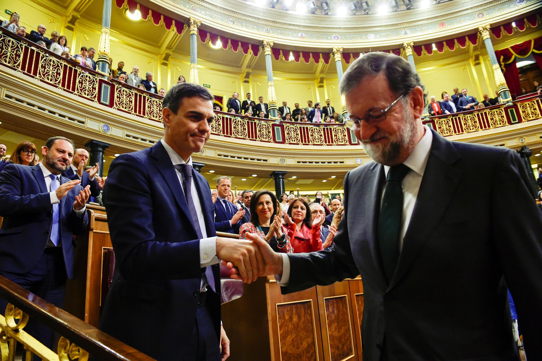 Новый премьер-министр Испании, социалист Педро Санчес (слева) пожимает руку Мариано Рахою, который потерял свой пост премьера из-за масштабного коррупционного скандала