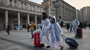 Pasajeros con mascarillas y trajes completos para protegerse se dirigen a la estación de Wuhan, en el centro de China, el 8 de abril de 2020
